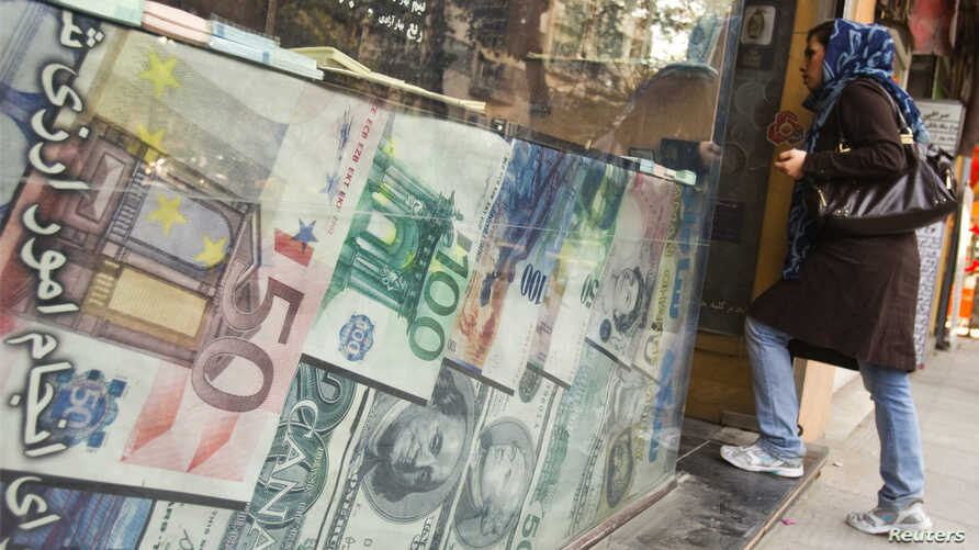 FILE - A woman enters a currency exchange shop in Tehran's business district, Oct. 24, 2011.