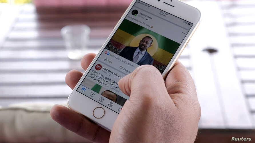 A man scrolls down his cell phone for social media newsfeed about Ethiopian Prime Minister Abiy Ahmed winning the Nobel Peace Prize in Addis Ababa, Ethiopia, Oct. 11, 2019.