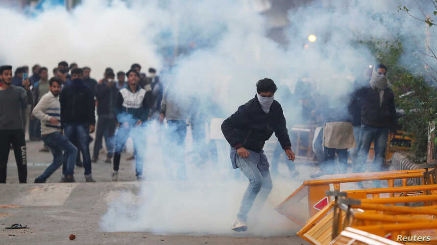 Protesters run for cover amid tear gas fired by police during a protest against the Citizenship Amendment Bill, New Delhi, Dec. 13, 2019.