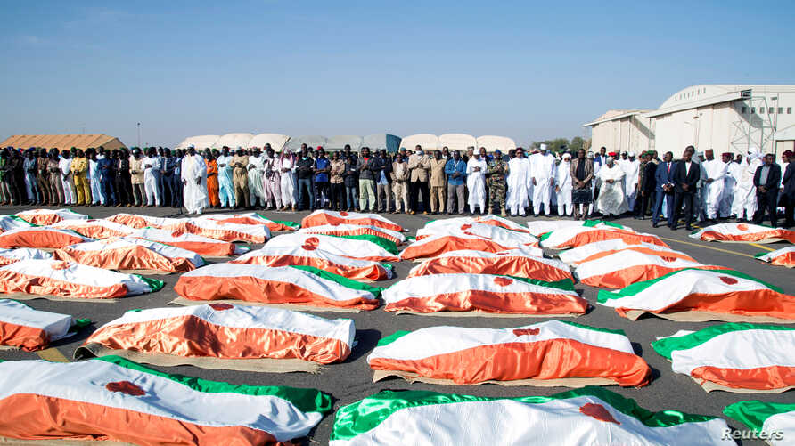 Families and officials pray in front of the flag-draped soldiers, killed during an attack on the army camp on the Niger- Mali…