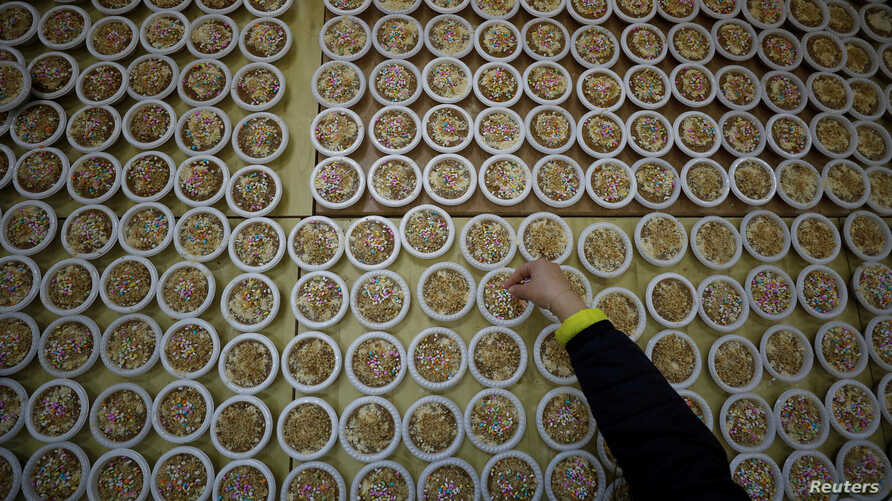 A woman arranges dishes of Burbara, a traditional food served during Saint Barbara's Day, in the village of Aboud, in the Israeli-occupied West Bank, Dec. 16, 2019.