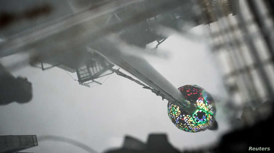 New Year's Eve ball at the roof of One Times Square building is reflected in a puddle during the New Year's Eve Ball test,…