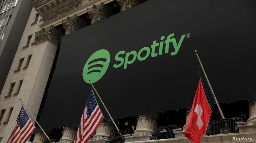 The Spotify logo hangs on the facade of the New York Stock Exchange with U.S. and a Swiss flag as the company lists it's stock…