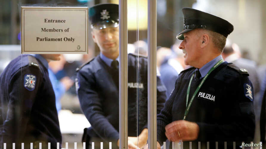 Police officers are seen inside the Parliament, as demonstrators block the streets around it, in Valletta, Malta, December 2,…