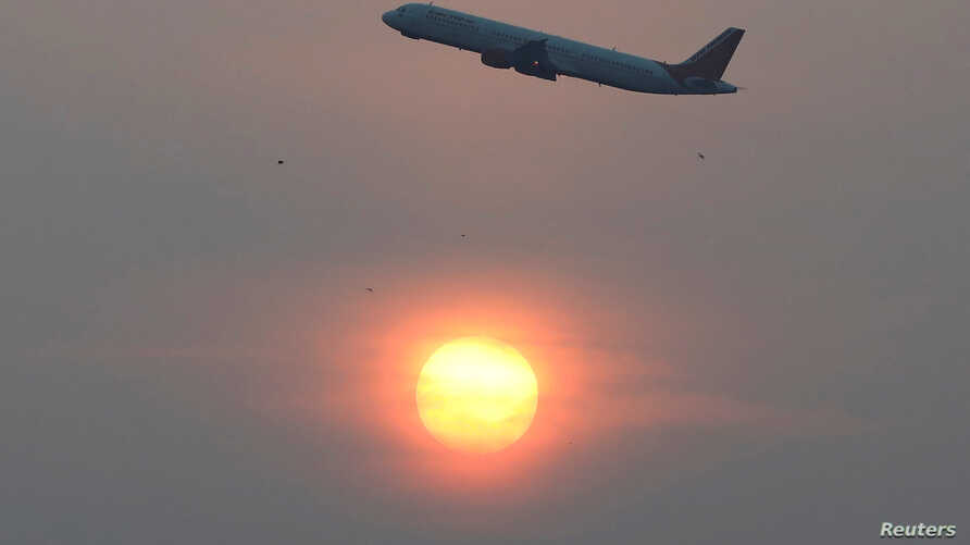 An Air India passenger plane passes the sun on a smoggy morning in Ahmedabad, India, December 4, 2019. REUTERS/Amit Dave -…
