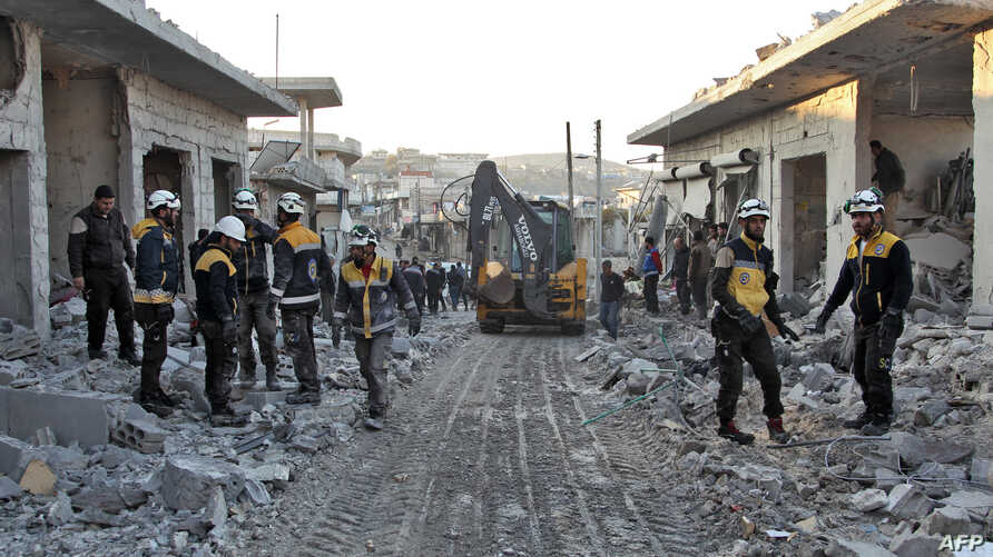 Members of the Syrian Civil Defense, also known as the White Helmets, stand with an excavator in a street filled with rubble and debris following a reported airstrike in the village of Balyun in Syria's northwestern Idlib province, Dec. 7, 2019.
