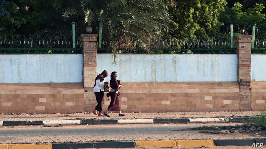 FILE - Two women walk, one freely without a headscarf, in the Sudanese capital Khartoum, Aug. 27, 2019.