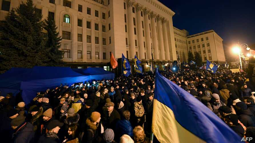"""Activists attend a """"Night Watch"""" rally in front of the Office of Ukraine's President, in Kyiv, Dec. 8, 2019, demanding """"no capitulation"""" ahead of Volodymyr Zelenskiy's talks with Russia's Vladimir Putin in Paris Monday."""