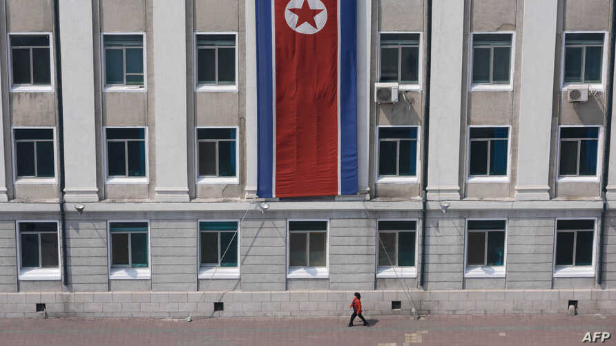 FILE - A pedestrian walks past a North Korean flag displayed on a building in Pyongyang, North Korea, April 12, 2019.