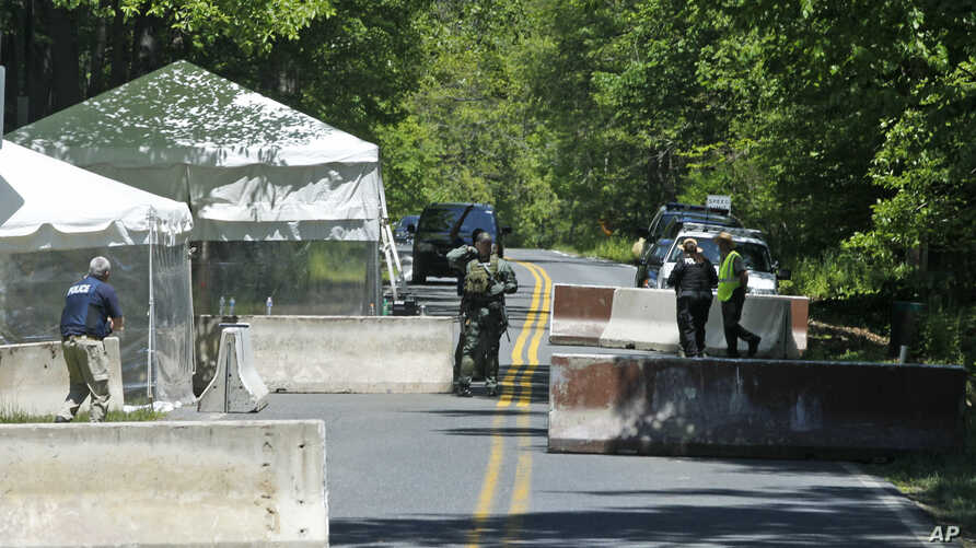 FILE - Security officials stand at a checkpoint outside of Camp Round Meadow, on the closed road leading up to the presidential retreat of Camp David, in Thurmont, Maryland, May 18, 2012.