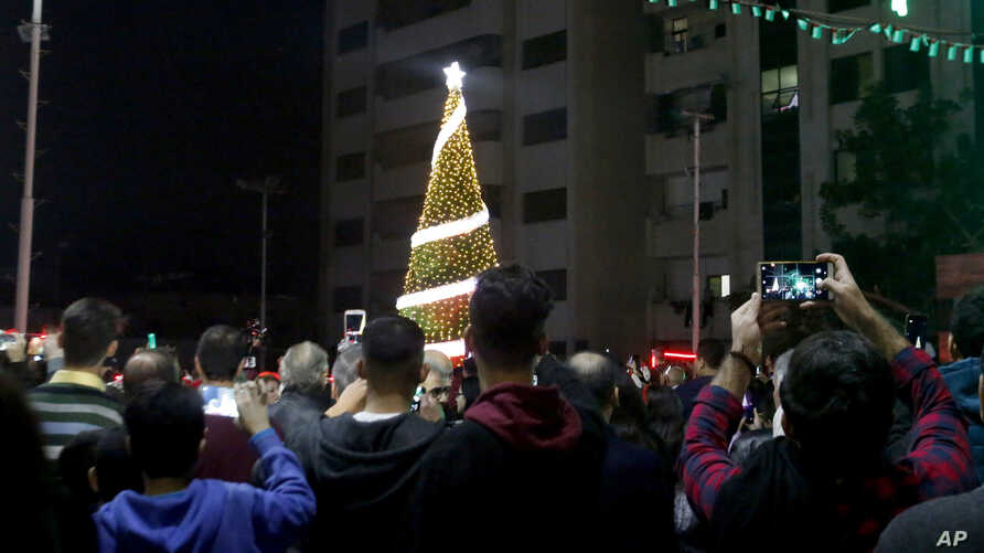 FILE - Palestinian Christians attend a Christmas tree lighting celebration in Gaza City, Dec. 3, 2019.