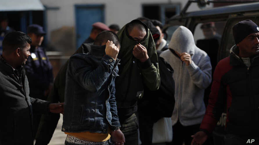 Detained Chinese people cover their faces as they are taken to a court in Kathmandu, Nepal, Dec 24, 2019.