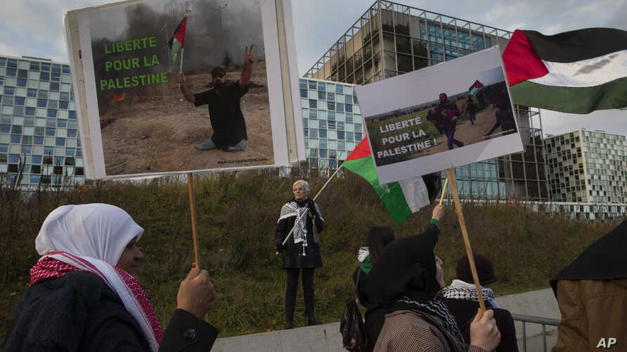 Demonstrators carry banners and Palestinian flags outside the International Criminal Court, ICC, urging the court to prosecute Israel's army for war crimes in The Hague, Netherlands, Nov. 29, 2019.