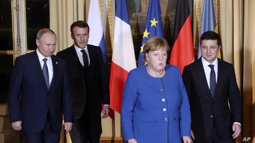 French President Emmanuel Macron, second left, Russian President Vladimir Putin, left, German Chancellor Angela Merkel and Ukrainian President Volodymyr Zelenskiy gather for talks at the Elysee Palace, in Paris, France, Dec. 9, 2019.