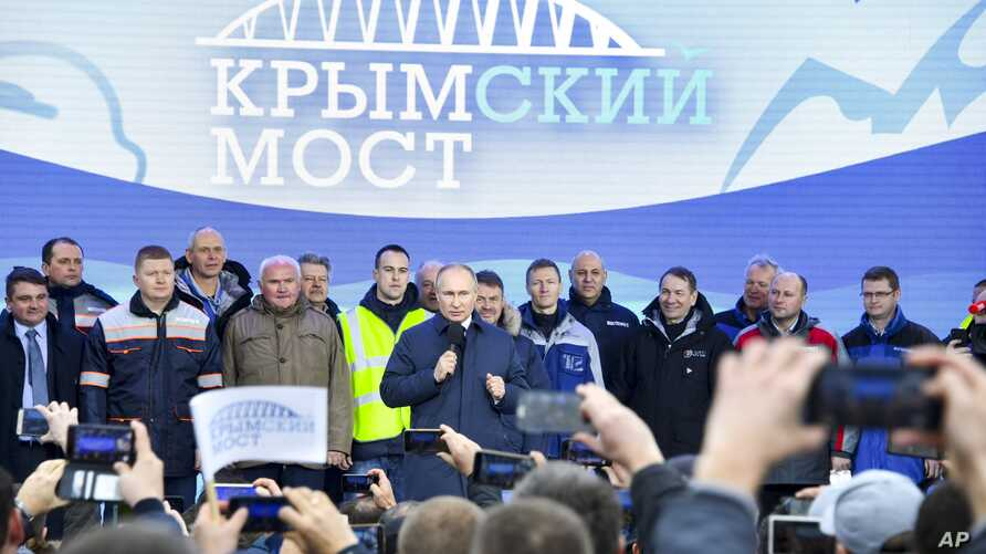Russian President Vladimir Putin, center, speaks to workers after riding a train across a bridge linking Russia and the Crimean peninsula in Taman, Russia, Dec. 23, 2019.