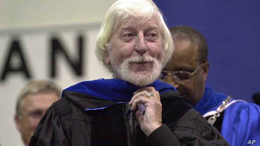 """FILE - Caroll Spinney, best known for his TV character """"Big Bird"""" from Sesame Street, receives an honorary doctorate from Eastern Connecticut State University President David G. Carter, rear, in Willimantic, Connecticut, May 21, 2000."""