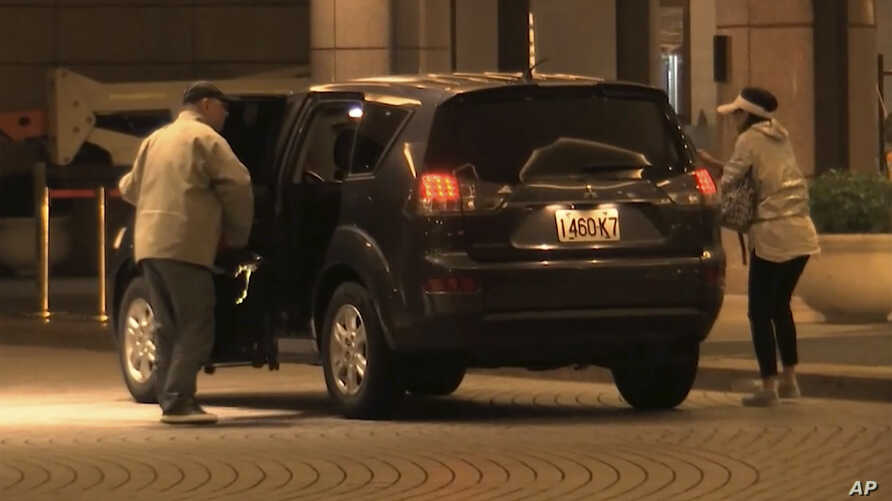 In image made from a video, China Innovation Investment Ltd. officials Xiang Xin and his wife Kung Ching get off a car at the Grand Hyatt hotel  in Taipei, Taiwan, Nov. 25, 2019.