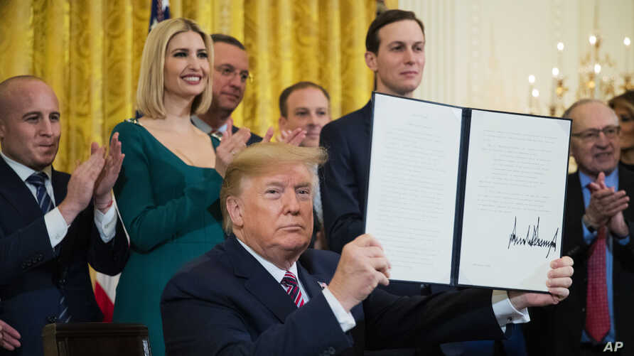 President Donald Trump holds up an executive order he signed to help combat anti-Semitism in the U. S., during a Hanukkah reception in the East Room of the White House, Dec. 11, 2019, in Washington.