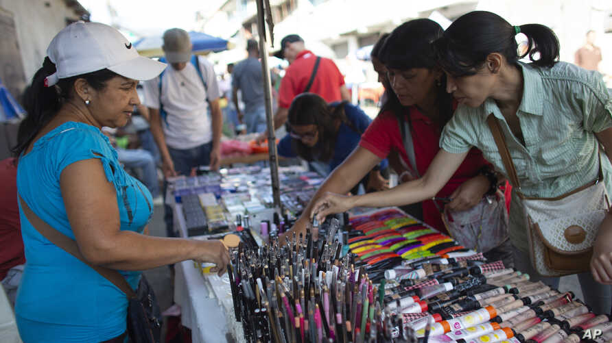 School teacher Daixy Aguero, left, sells makeup at a market in Caracas, Oct. 5, 2019. Aguero holds her chin up when students wander by surprised to spot their teacher selling makeup on weekends at a Caracas market.