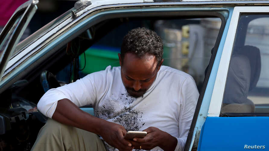 FILE - A taxi driver checks his smartphone as he waits for his customers in Addis Ababa, Ethiopia, Nov. 12, 2019.