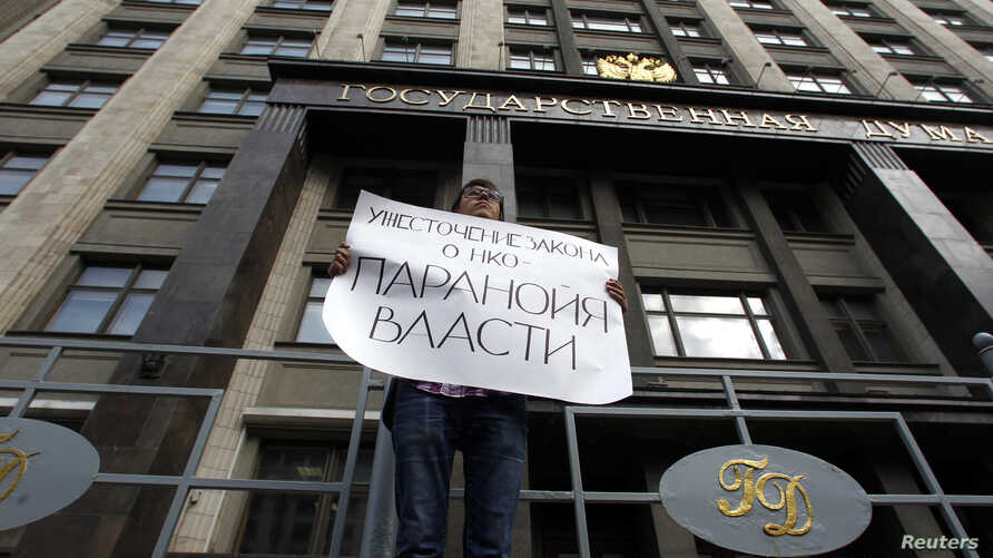 "FILE - A lone protester demonstrates against the original NGO foreign agent law, outside the Duma, Russia's lower house of parliament, in Moscow, Russia, July 6, 2012. The placard reads ""Tightening the NGO law speaks to the paranoia of authorities."""
