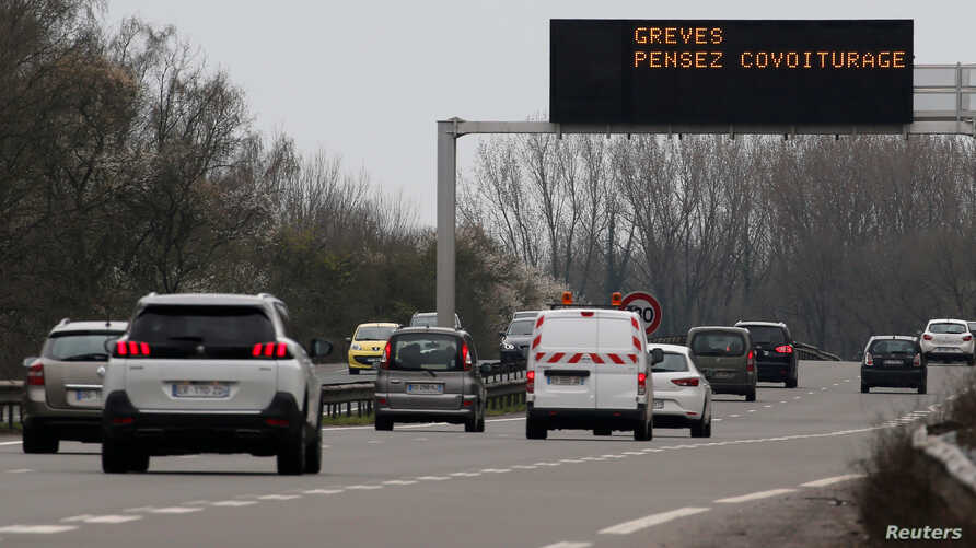 "FILE - Motorists drive on the Lille-Valenciennes highway as an illuminated road sign reads ""Strikes, think carpooling,"" in Raismes, France, April 2, 2018."