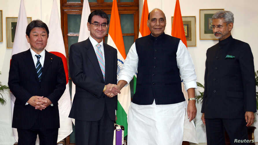 India's Defense Minister Rajnath Singh shakes hands with his Japanese counterpart Taro Kono as India's Foreign Minister Subrahmanyam Jaishankar and Japan's Foreign Minister Toshimitsu Motegi look on, in New Delhi, India, Nov. 30, 2019.