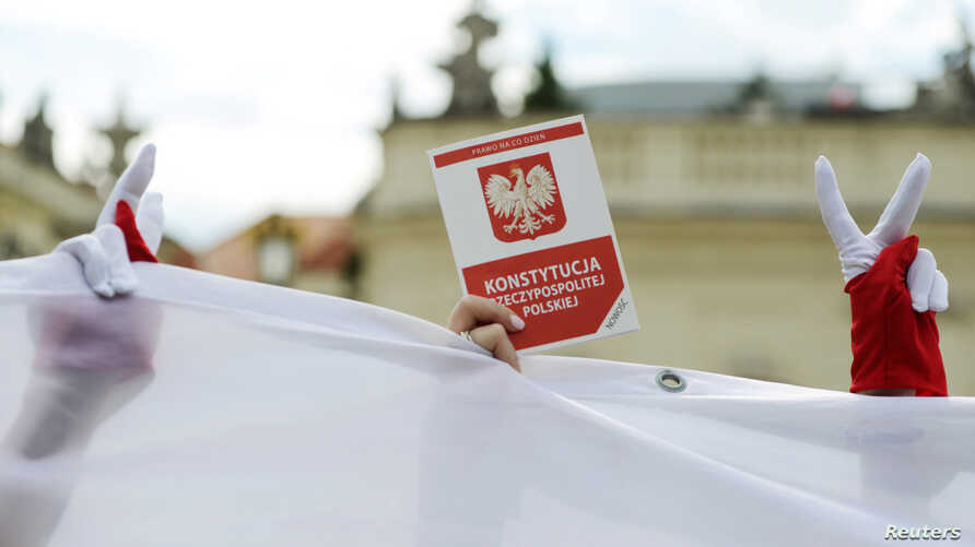 FILE - A demonstrator holds a copy of the Polish Constitution during a protest against judicial reforms, outside the Presidential Palace in Warsaw, Poland, July 3, 2018.