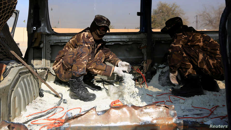 FILE - Afghan security personnel inspect a car filled with explosives which was seized from a Taliban insurgent in Jalalabad, Afghanistan Dec. 10, 2019.