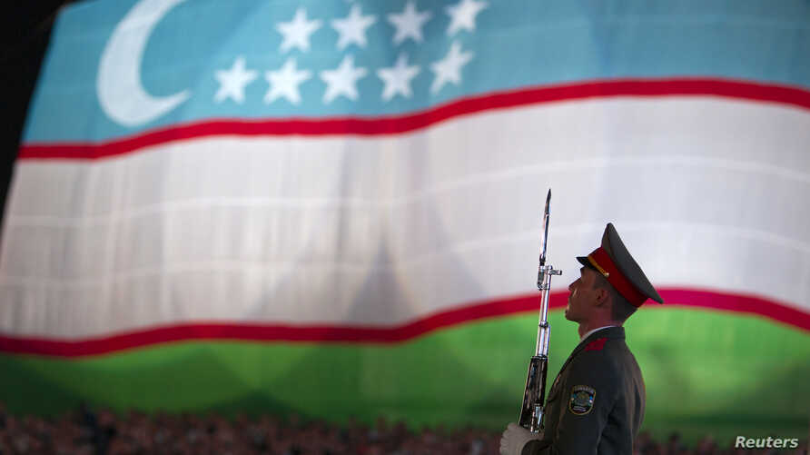 FILE - A soldier stands in front of the national flag of Uzbekistan during an Independence Day celebration in Tashkent, Aug. 31, 2012.