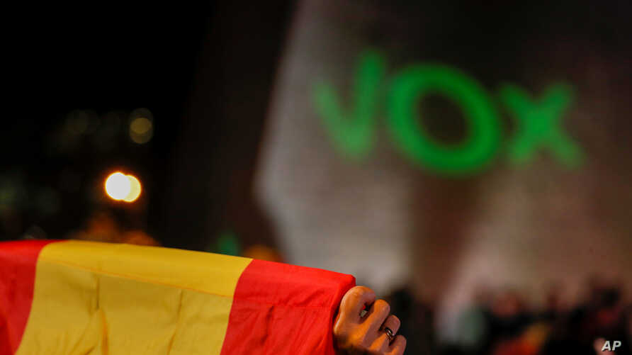 FILE - A supporter of Spain's far-right party Vox holds a Spanish flag during a campaign closing rally ahead of the general election, at Colon square in Madrid, Spain, Nov. 8, 2019.