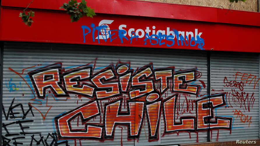 FILE - A Scotiabank gate is seen graffitied during a protest against Chile's government in Santiago, Chile, Nov. 1, 2019.