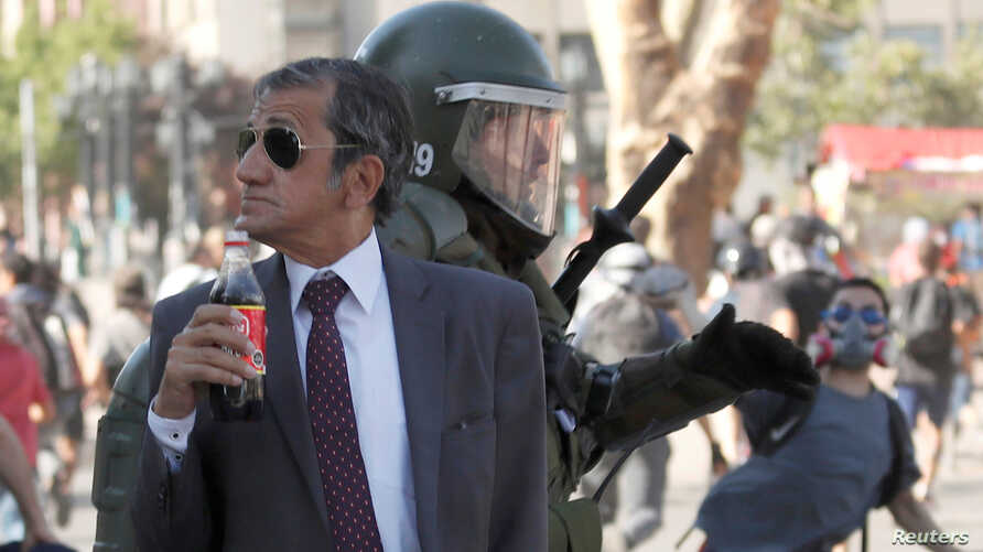 FILE - A man drinks a Frucola as a police officer chases demonstrators during a protest against Chile's government in Santiago, Chile, Dec. 4, 2019.
