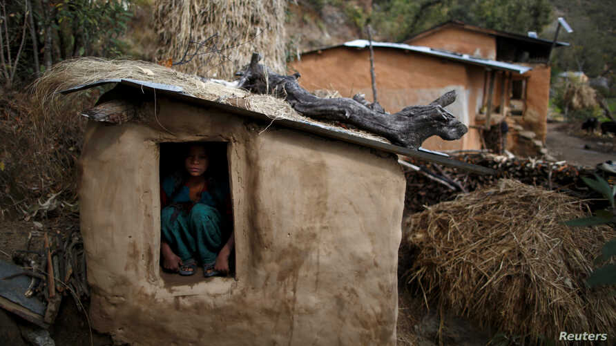 Uttara Saud, 14, sits inside a Chhaupadi shed in the hills of Legudsen village in Achham District in western Nepal, February 16,…