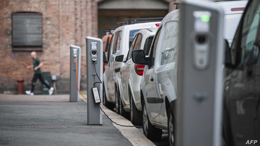 Electric cars are being charged on a street in the Norwegian capital Oslo on April 30, 2019. - Rich or not, young and old, hip…