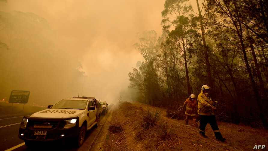 Firefighters tackle a bushfire in thick smoke in the town of Moruya, south of Batemans Bay, in New South Wales, Jan. 4, 2020. Up to 3,000 military reservists were called up to tackle Australia's bushfires as tens of thousands of people fled.