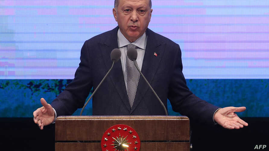 Turkish President Recep Tayyip Erdogan delivers a speech as he stands in front of a huge screen during the Annual Evaluation…