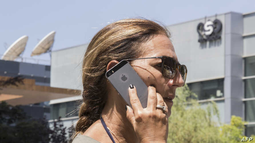 FILE - An Israeli woman uses her iPhone in front of the building housing the Israeli NSO group, Aug. 28, 2016, in Herzliya, near Tel Aviv.