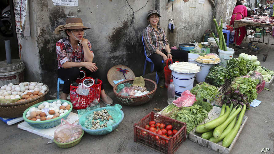 A woman sells vegetables at an outdoor market in Hanoi, Vietnam, Feb. 21, 2019.