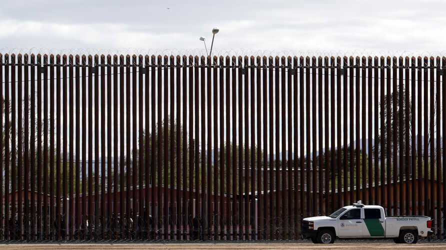 In this April 5, 2019, photo, a U.S. Customs and Border Protection vehicle sits near the a section of the U.S. border wall with…