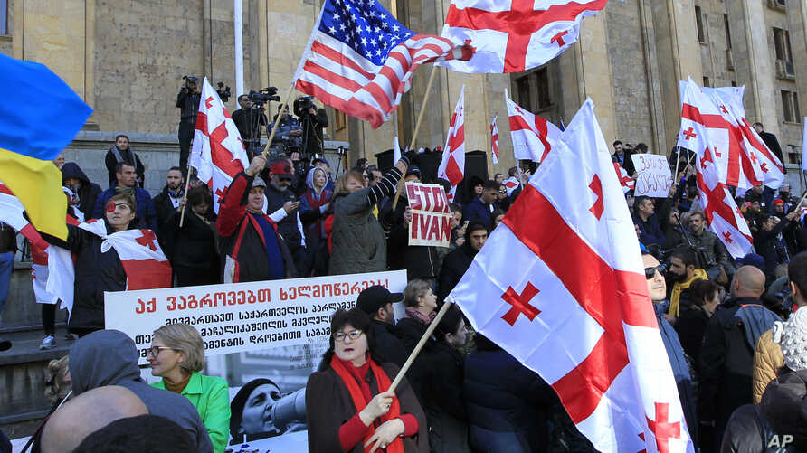 Demonstrators wave Georgian and American, center left, flags as they gather at the Georgian parliament building in Tbilisi,…