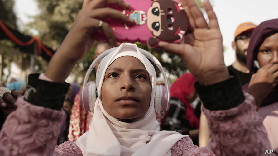 FILE - A teenager films Sudanese dancers on her mobile phone during an event marking the U.N.'s International Refugee Day, in Cairo, Egypt, June 20, 2019.