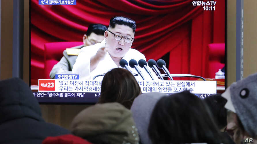People watch a TV screen showing a file image of North Korean leader Kim Jong Un during a news program at the Seoul Railway…
