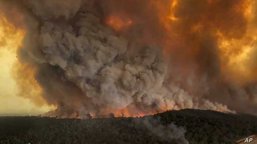 In this Monday, Dec. 30, 2019, aerial photo, wildfires rage under plumes of smoke in Bairnsdale, Australia. Thousands of…