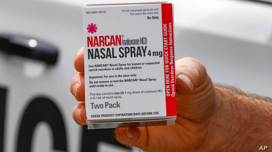 FILE - In this Thursday, Sept. 12, 2019 file photo, a police officer holds a box of Narcan, a drug used to treat opioid…