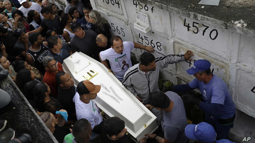 FILE - In this Sept. 22, 2019 file photo, people carry the coffin of Agatha Sales Felix, who was hit by a a stray bullet, at a…