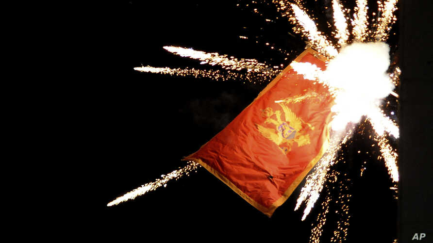 The Montenegrin flag flying from the Montenegrin Embassy, is targeted with fireworks by Serbian ultra-nationalists during a protest against a religion rights law adopted by Montenegro's parliament last month, during a mass protest in Belgrade, Serbia, Jan. 2, 2020.