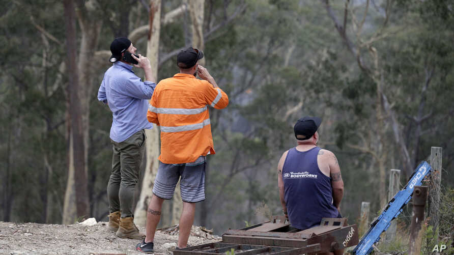 Residents on edge of Batemans Bay, Australia, relax after a fire threat near their homes eased Saturday, Jan. 4, 2020.