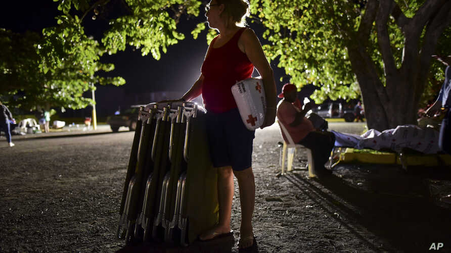 A woman holds a blanket and cots as neighbors remain outdoors using camping tents and portable lights for fear of possible aftershocks after a 6.4-magnitude earthquake struck in Guanica, Puerto Rico, Tuesday, Jan. 7, 2020. The quake was followed by a series of strong aftershocks, part of a 10-day series of temblors spawned by the grinding of tectonic plates along three faults beneath southern Puerto Rico. (AP Photo/Carlos Giusti)