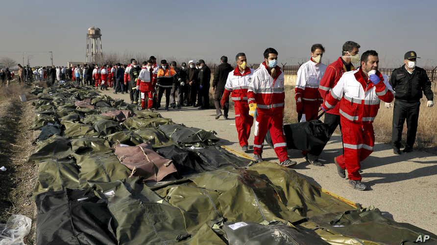 Rescue workers carry the body of a victim of a Ukrainian plane crash in Shahedshahr, southwest of the capital Tehran, Iran.